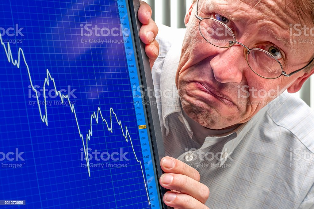 frowning man and sinking stock exchange rate on monitor stock photo