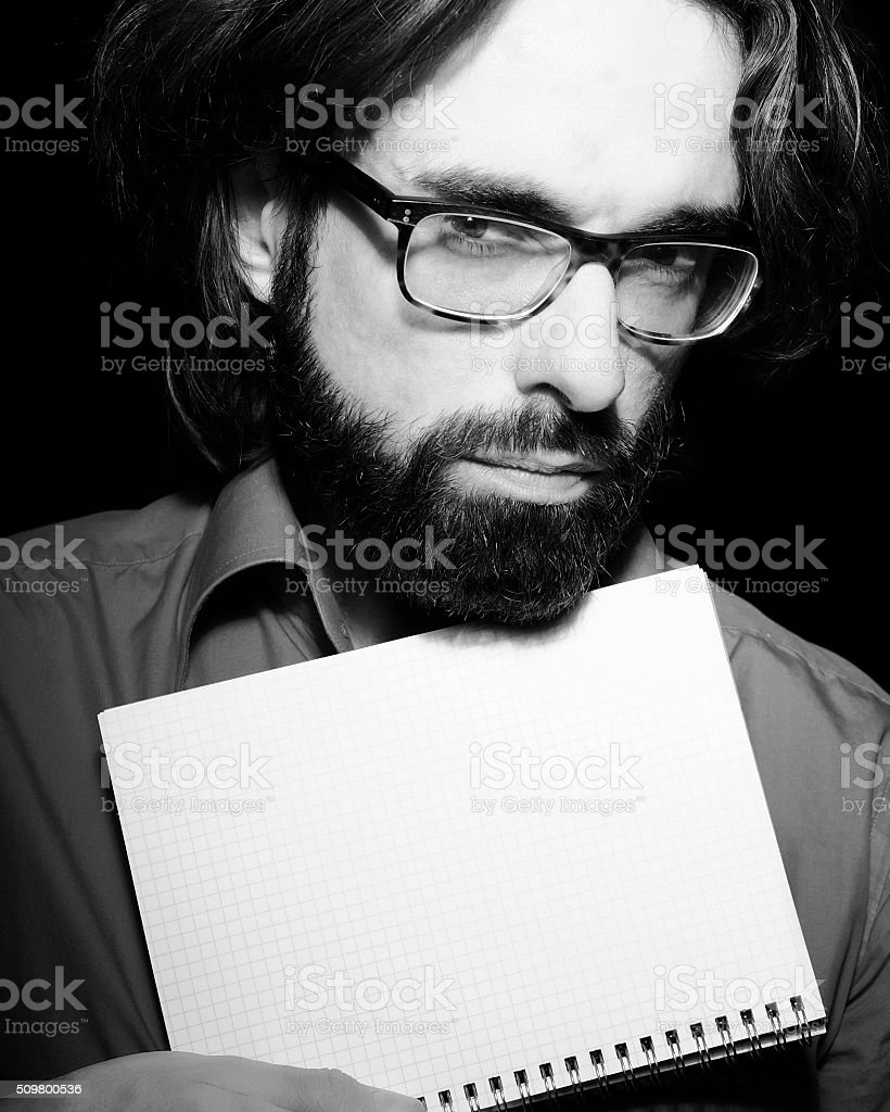 Frowning man holds sketchbook for copyspace stock photo