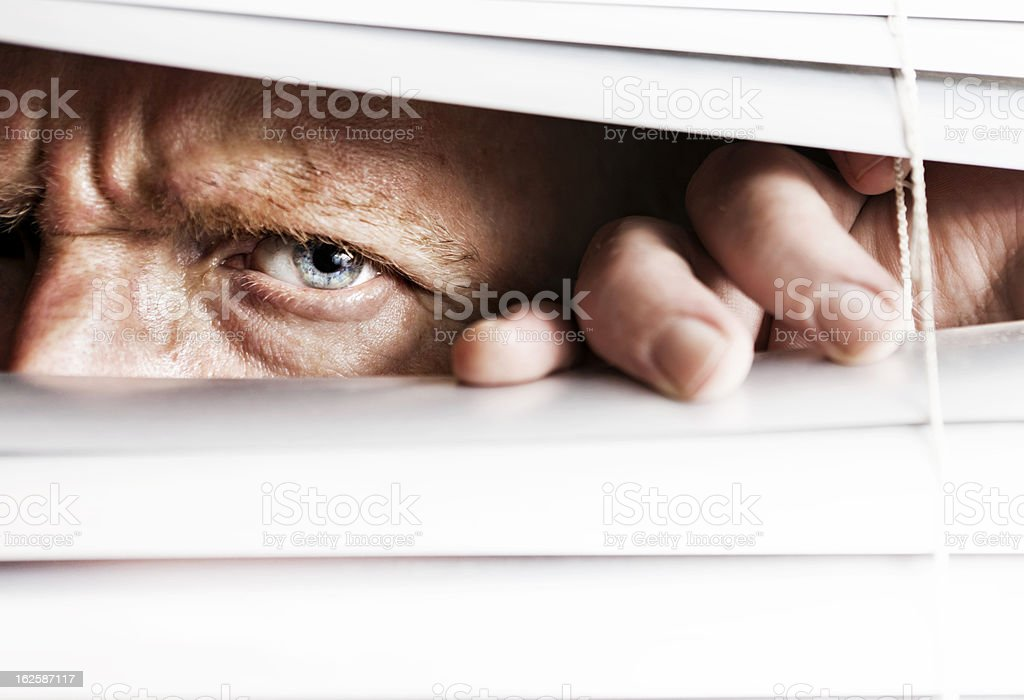Frowning man peeps through venetian blinds stock photo