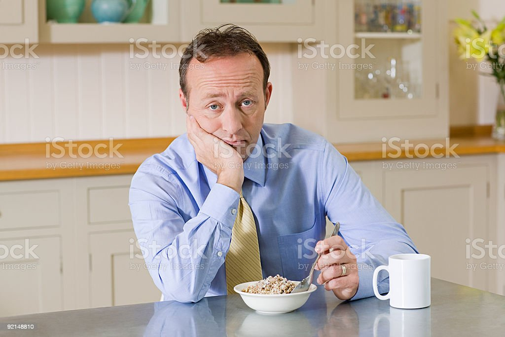 Frowning man with breakfast stock photo