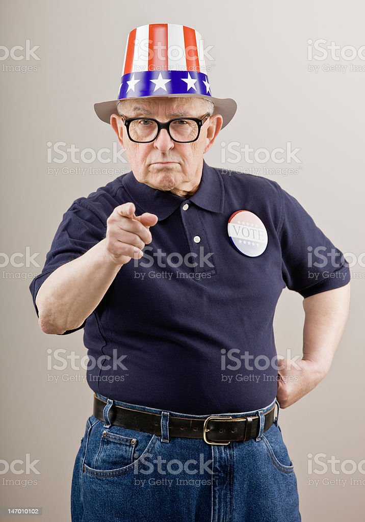 Frowning patriotic man in American hat and vote button royalty-free stock photo