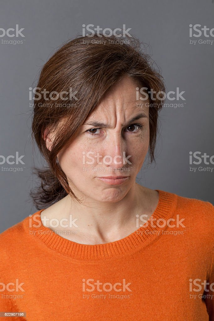 frowning woman having doubts complaining and grumbling with irritation stock photo