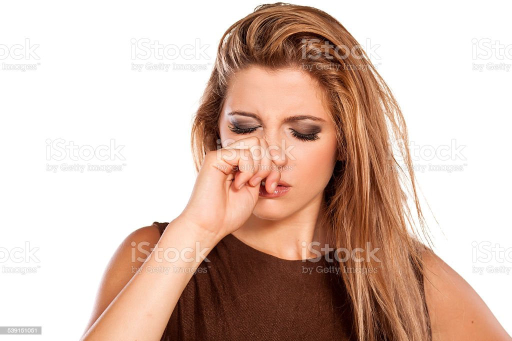 Frowning young woman scratching her nose stock photo