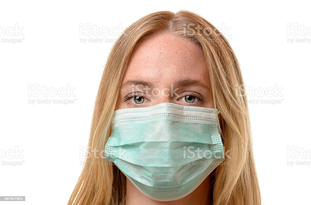 Frowning young woman wearing a face mask stock photo