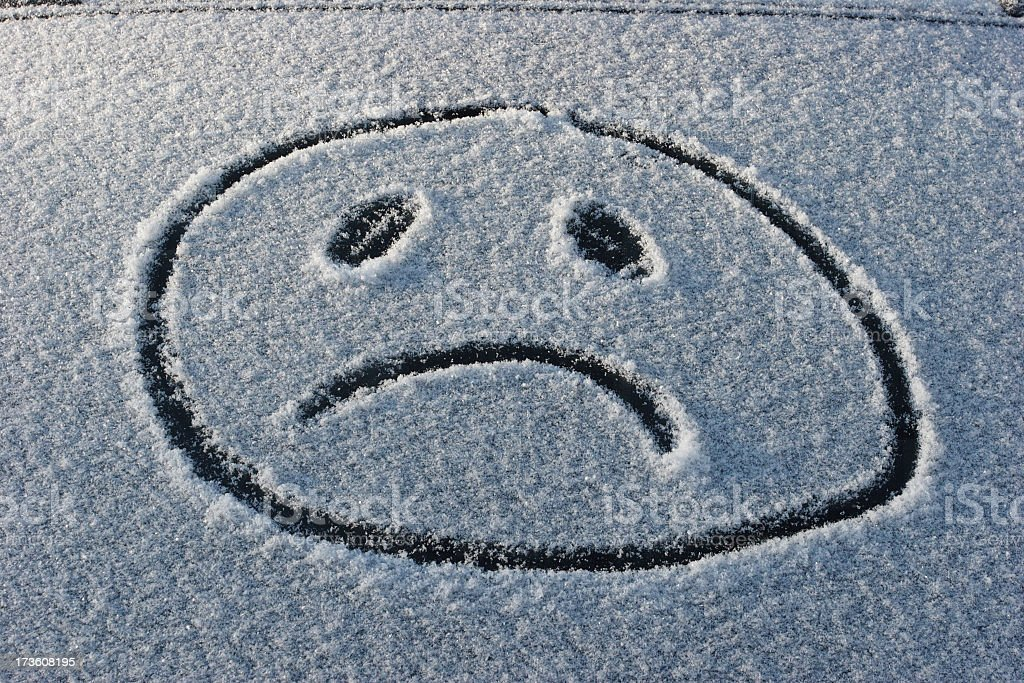 A frowny face has been drawn in the snow  royalty-free stock photo