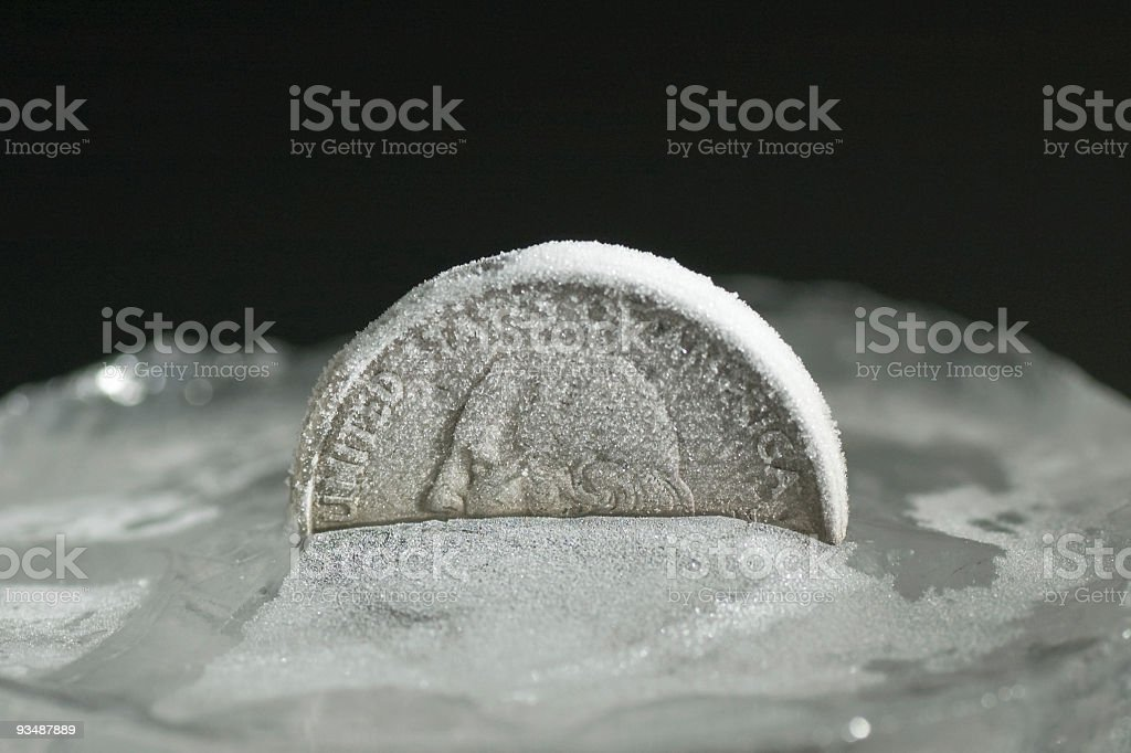 Financial crisis of bank business - coin frozen in ice stock photo