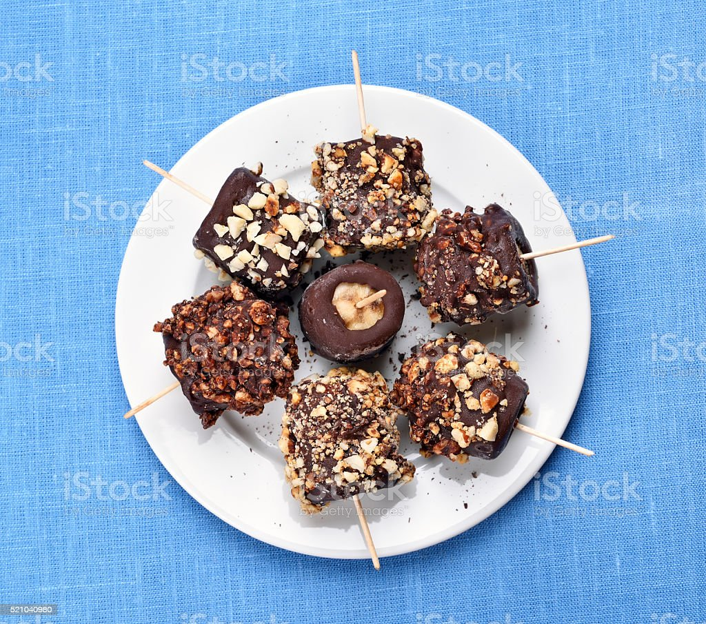 Frozen banana covered with chocolate stock photo