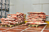 Frozen beef carcasses are stacked on pallets for cold storage.