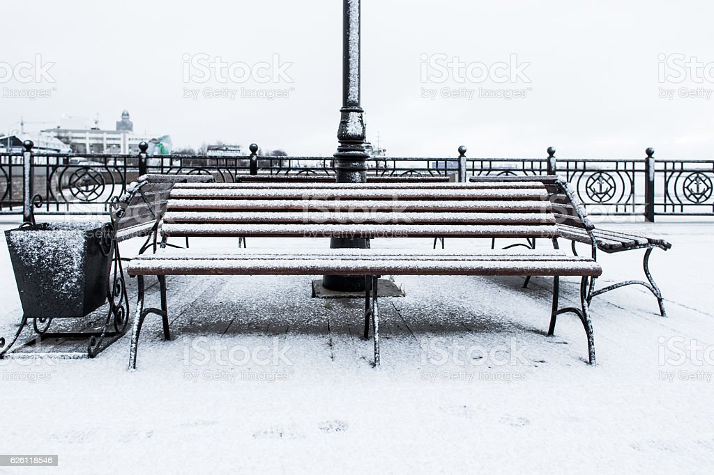 Frozen bench covered gritty rough hoarfrost on a cloudly winter stock photo