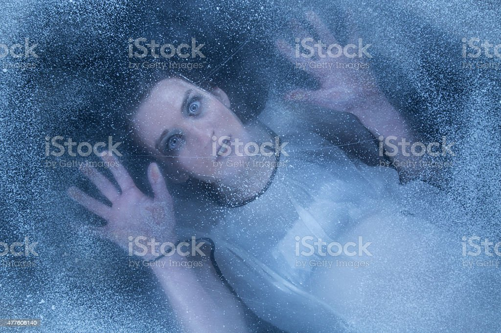 Frozen body under the ice stock photo