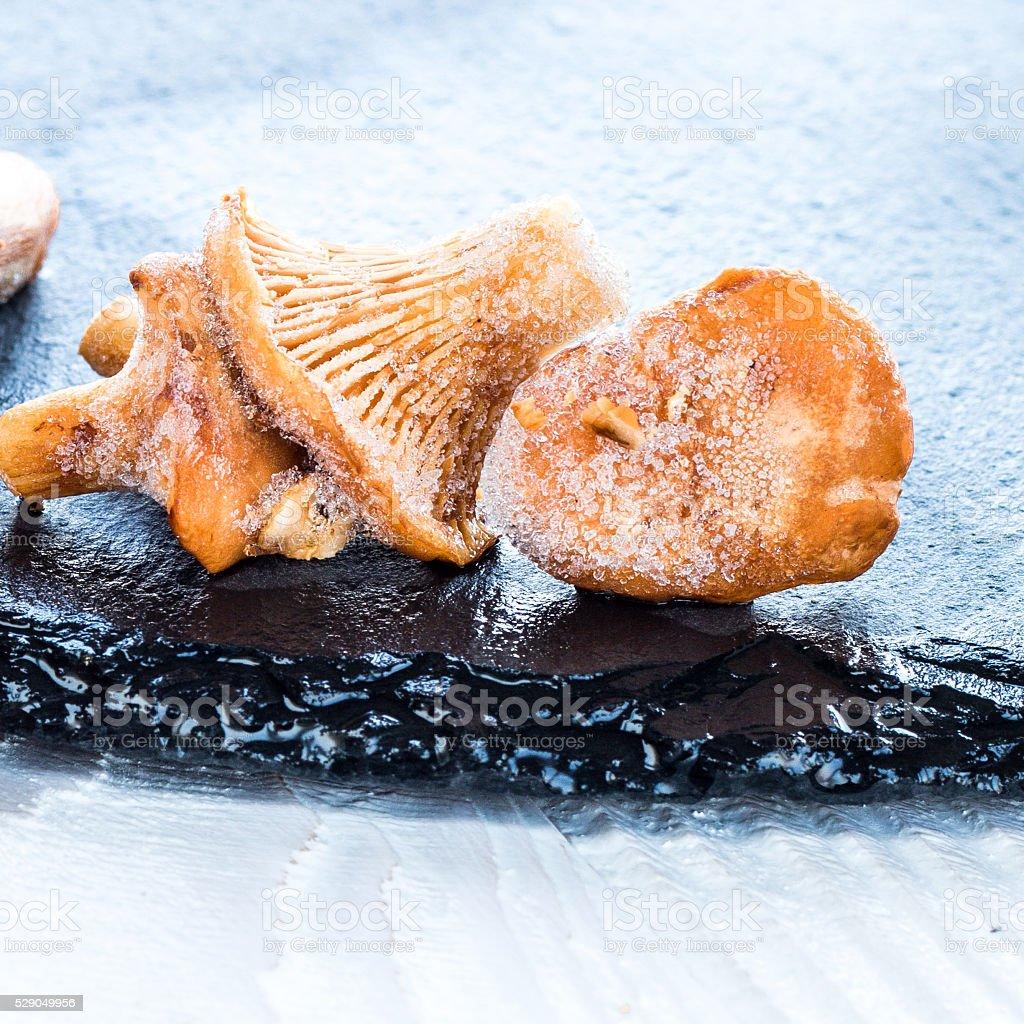 frozen chanterelles on black stone tray stock photo