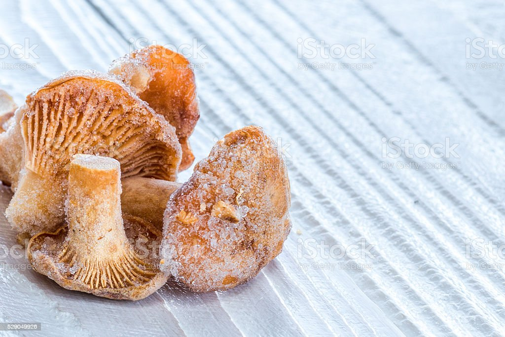 frozen chanterelles on white colored wooden table stock photo
