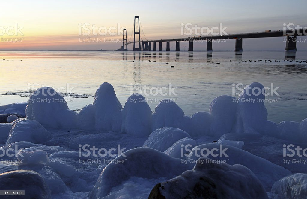 Frozen coastline and sunset at the Great Belt Bridge stock photo