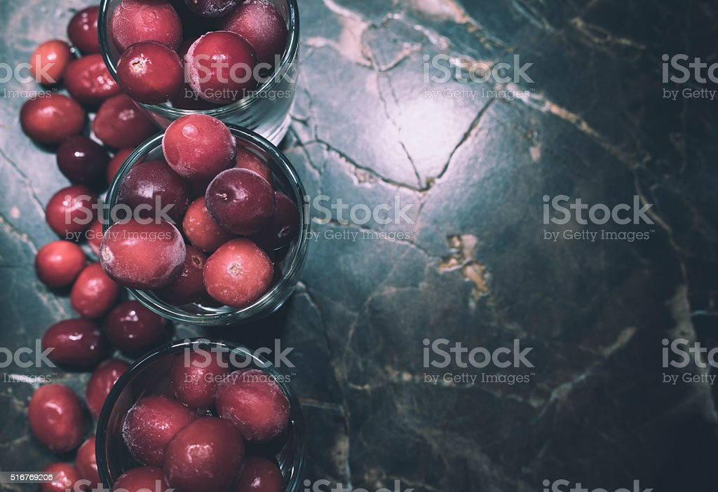 Frozen cow berries on a stone table stock photo