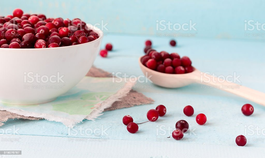 Frozen Cranberries in Bowl on blue desk stock photo