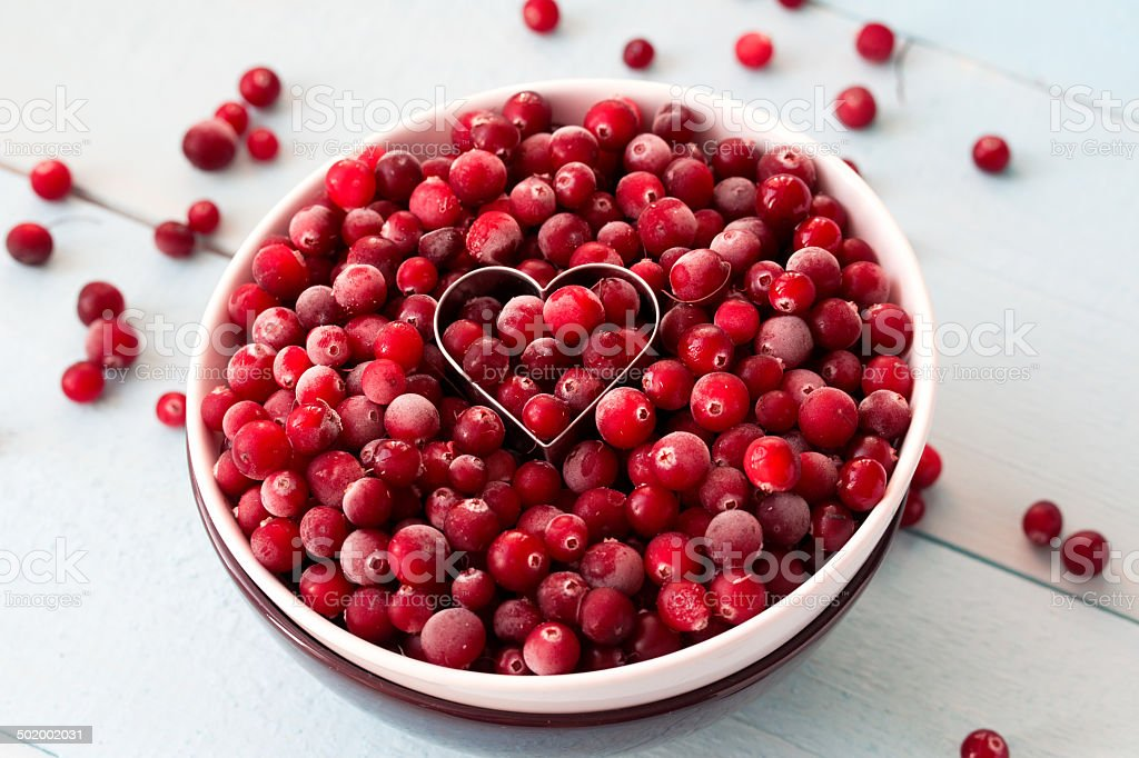 Frozen Cranberries in Bowl within heart shaped cookie cutter stock photo