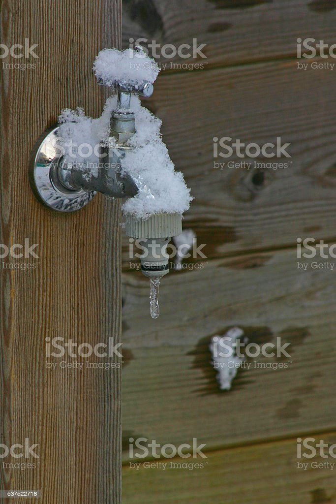 Frozen faucet with snow and icicle stock photo