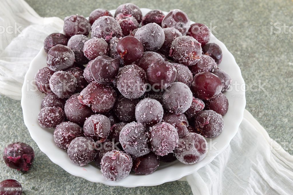 Frozen grapes in a white bowl stock photo