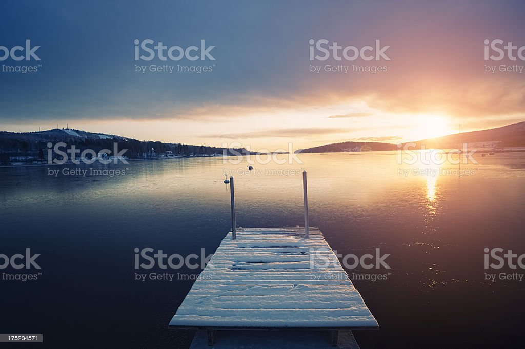 Frozen jetty on the lake during winter at sunset royalty-free stock photo