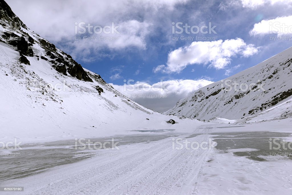 Frozen lake between snow mountains stock photo