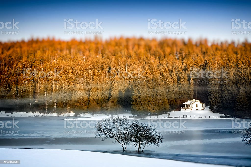 Frozen lake in winter with small remote cabin in forest stock photo