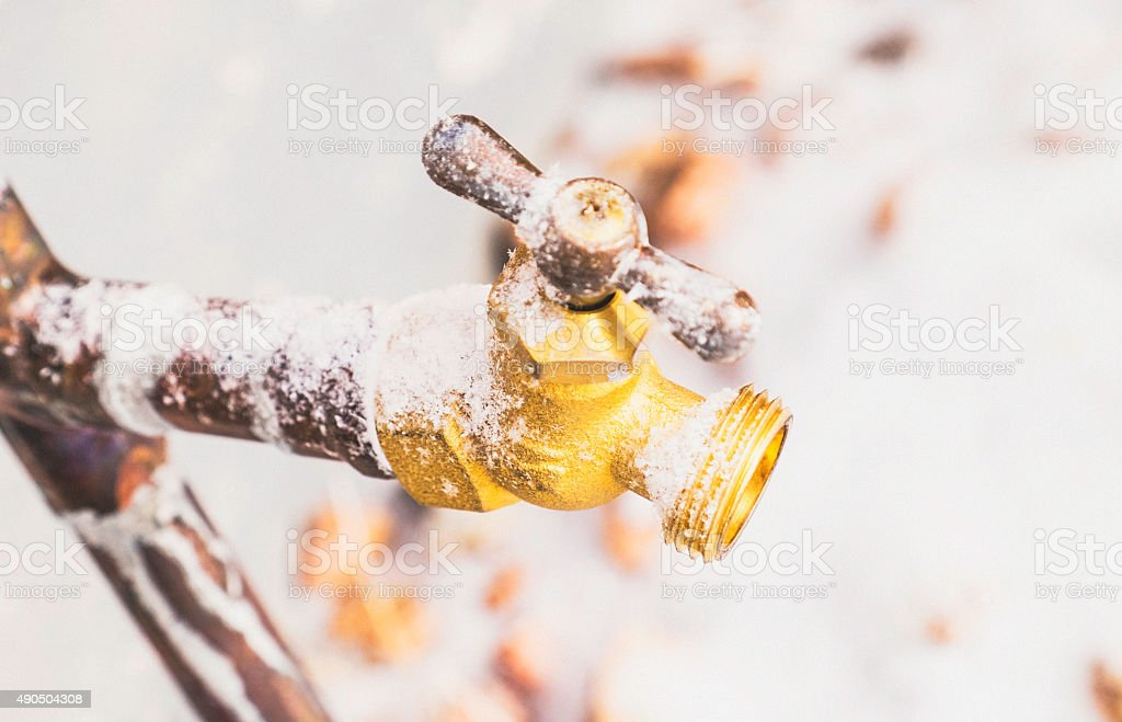 Frozen outdoor water faucet covered in snowflakes stock photo