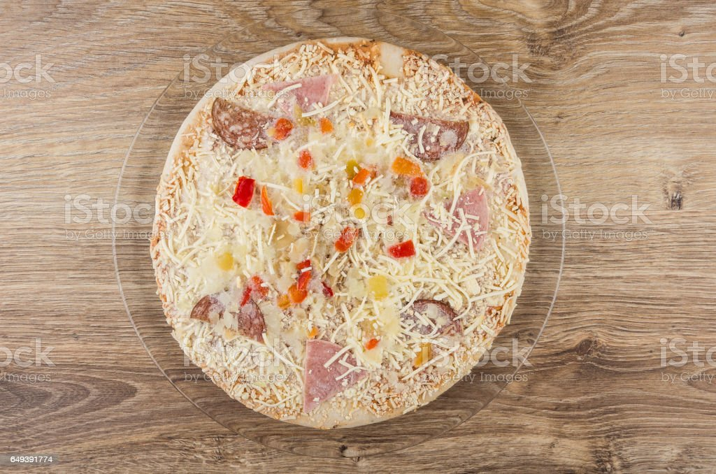 Frozen pizza with sausage in transparent dish on wooden table stock photo