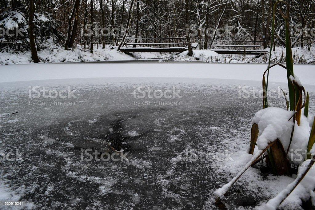 Frozen pond with bridge in background stock photo