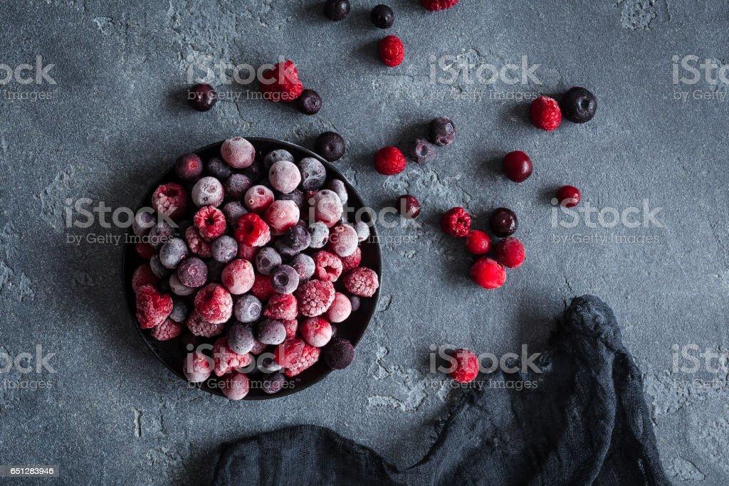 Frozen raspberry, blueberry, cranberry on dark background stock photo