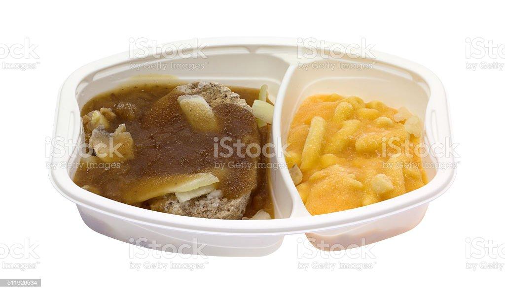 Frozen Salisbury steak TV dinner in white plastic tray stock photo