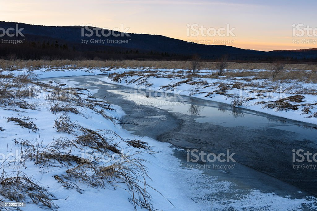 Frozen Stream and Snow Covered Field at Sunset stock photo
