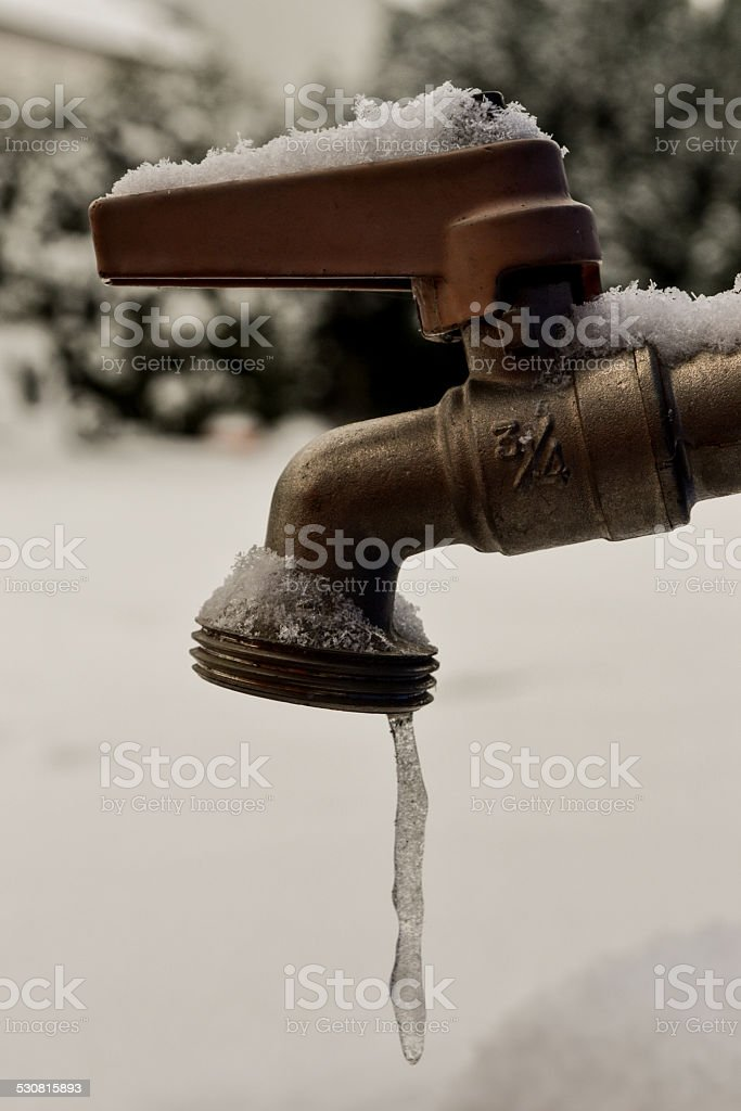 Frozen water coming from tap, droplet freezes stock photo