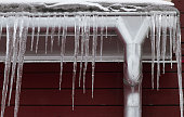 Frozen water pipe with icicles. Cold weather concept. Brown wooden
