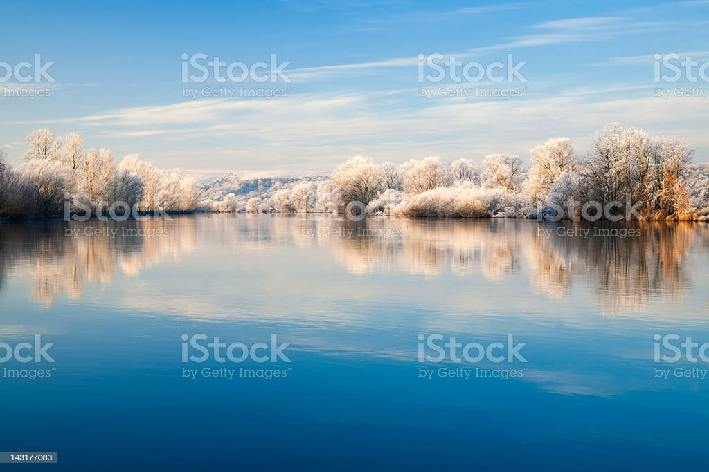 Frozen Winter Landscape with Trees Reflecting in River at Sunrise royalty-free stock photo