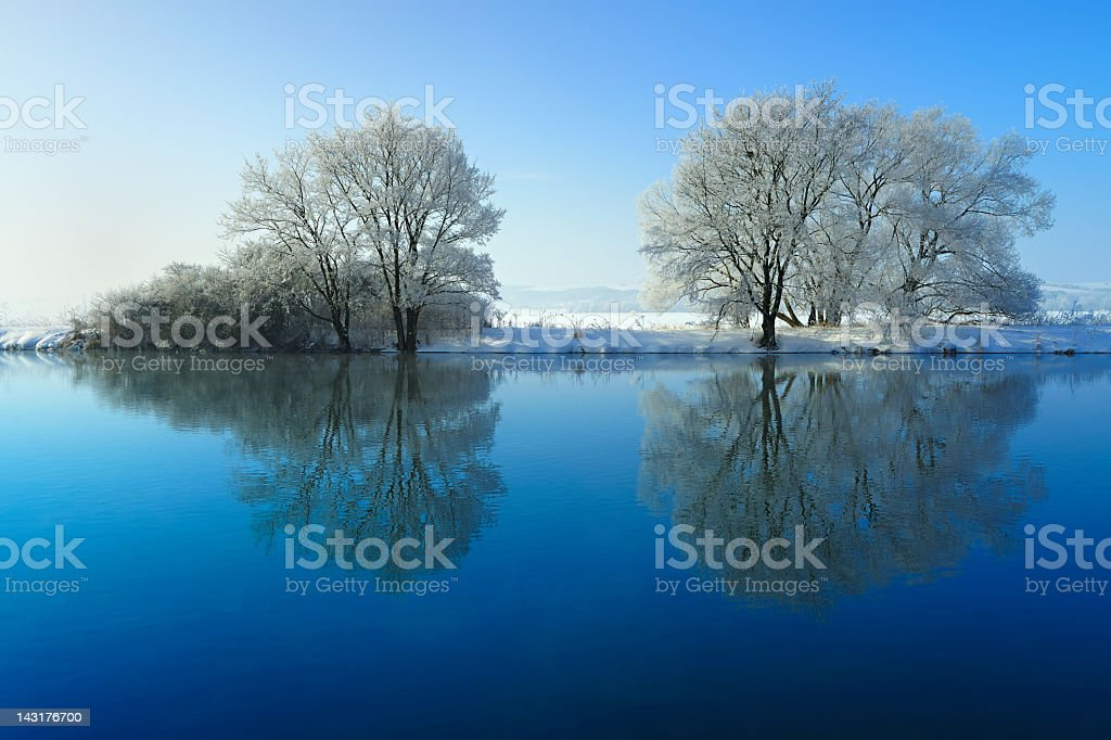 Frozen Winter Landscape with Trees Reflecting in River royalty-free stock photo