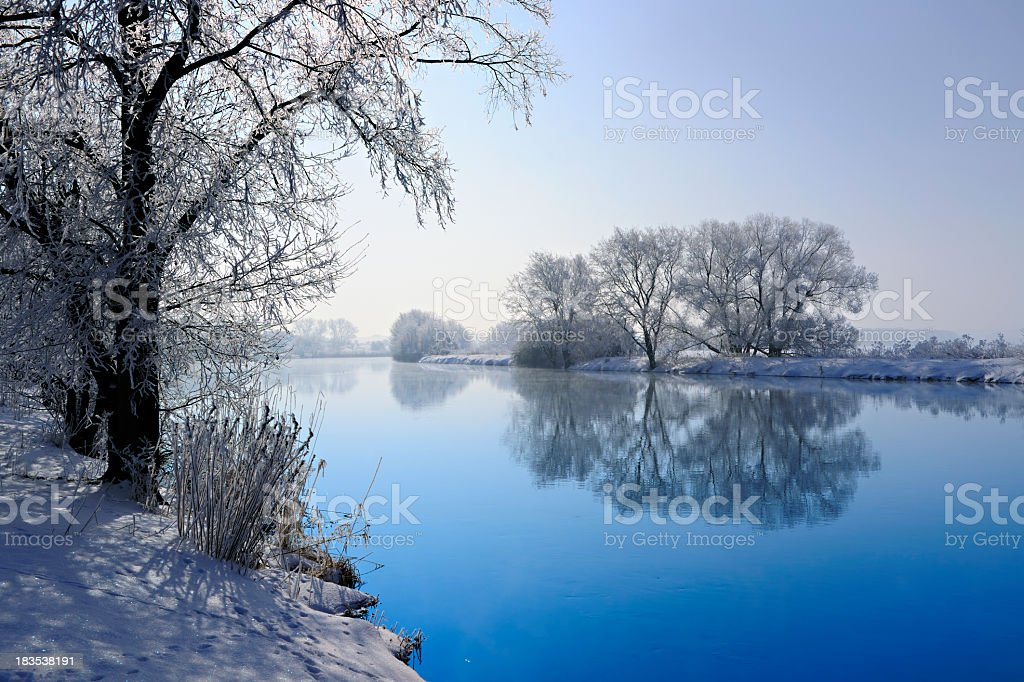 Frozen Winter Landscape with Trees Reflecting in River stock photo
