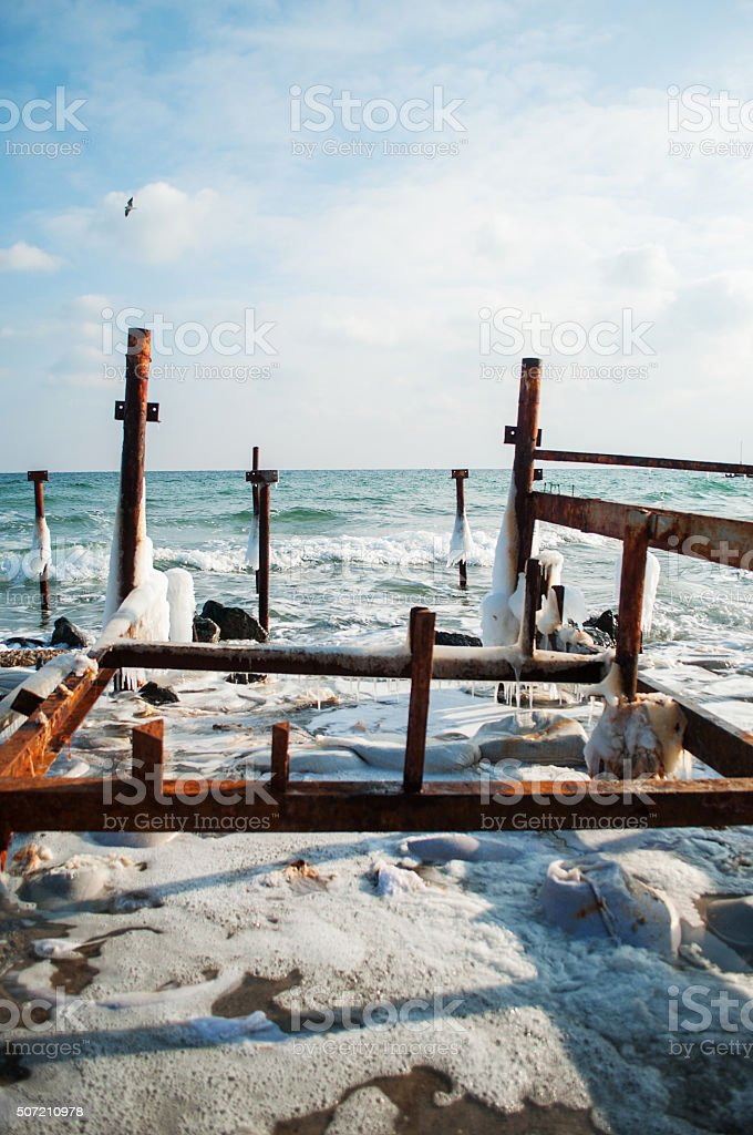 Frozen winter sea with wooden pole. Vertical stock photo