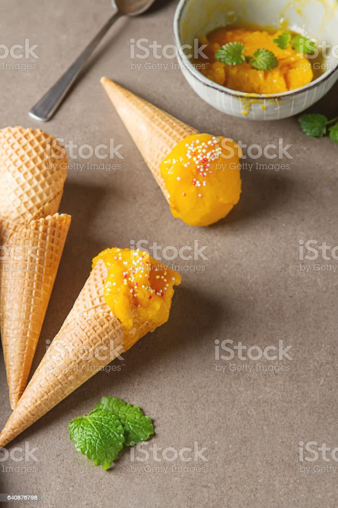 Frozen yellow mango sorbet, berry ice cream cone with mint and b stock photo