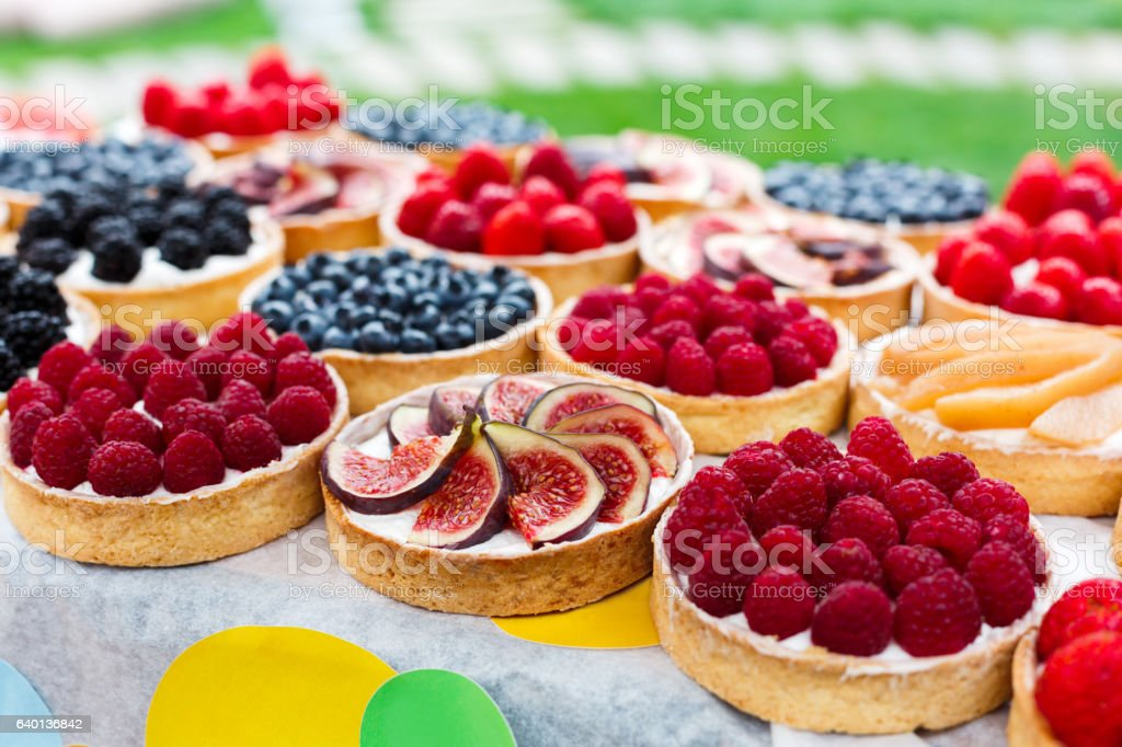 Fruit and berry tarts dessert tray assorted outdoors stock photo