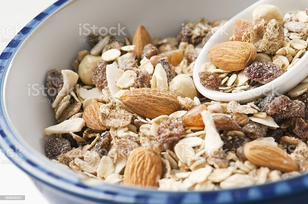 Fruit and nut muesli in blue rimmed bowl with spoon stock photo