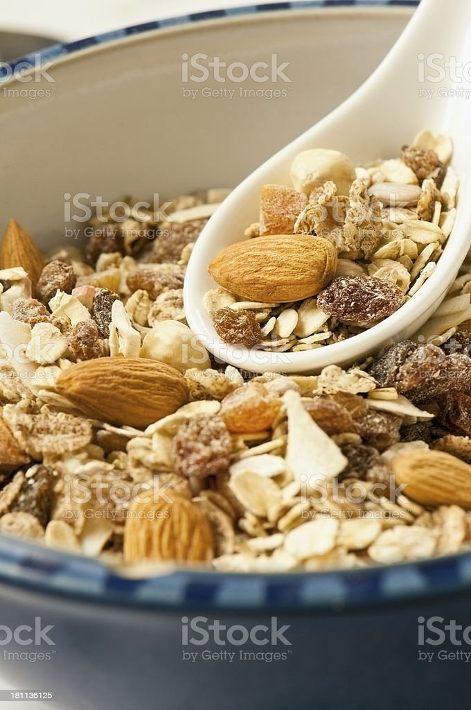 Fruit and nut muesli in breakfast bowl with spoon stock photo