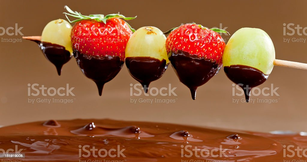 Fruit being dipped in chocolate fondue royalty-free stock photo
