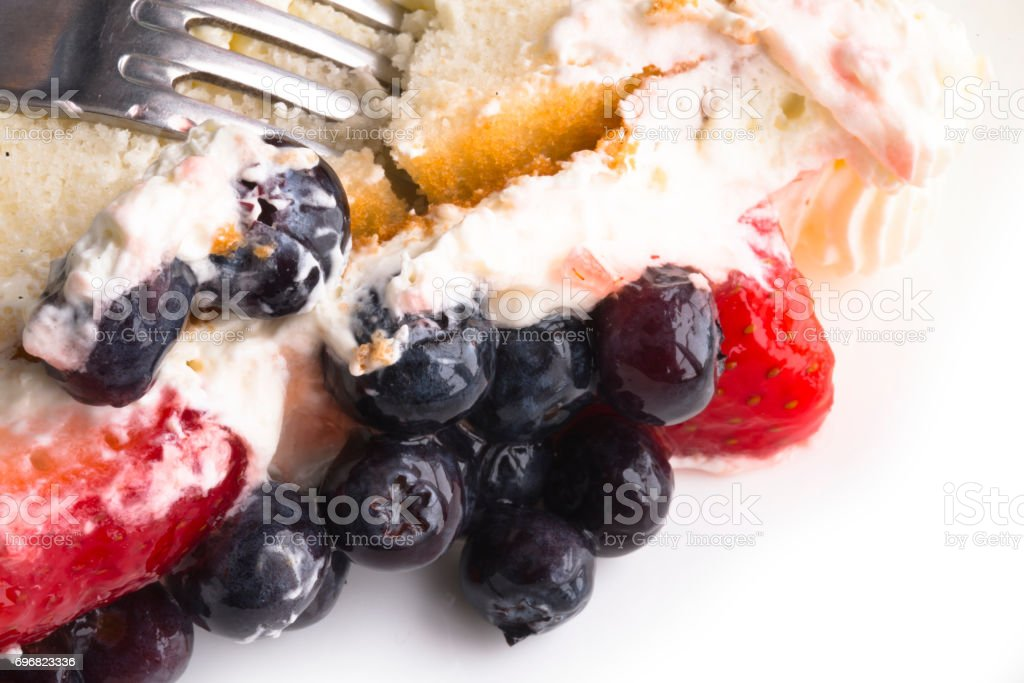 Fruit cake with strawberries and blueberries in sweet cream stock photo