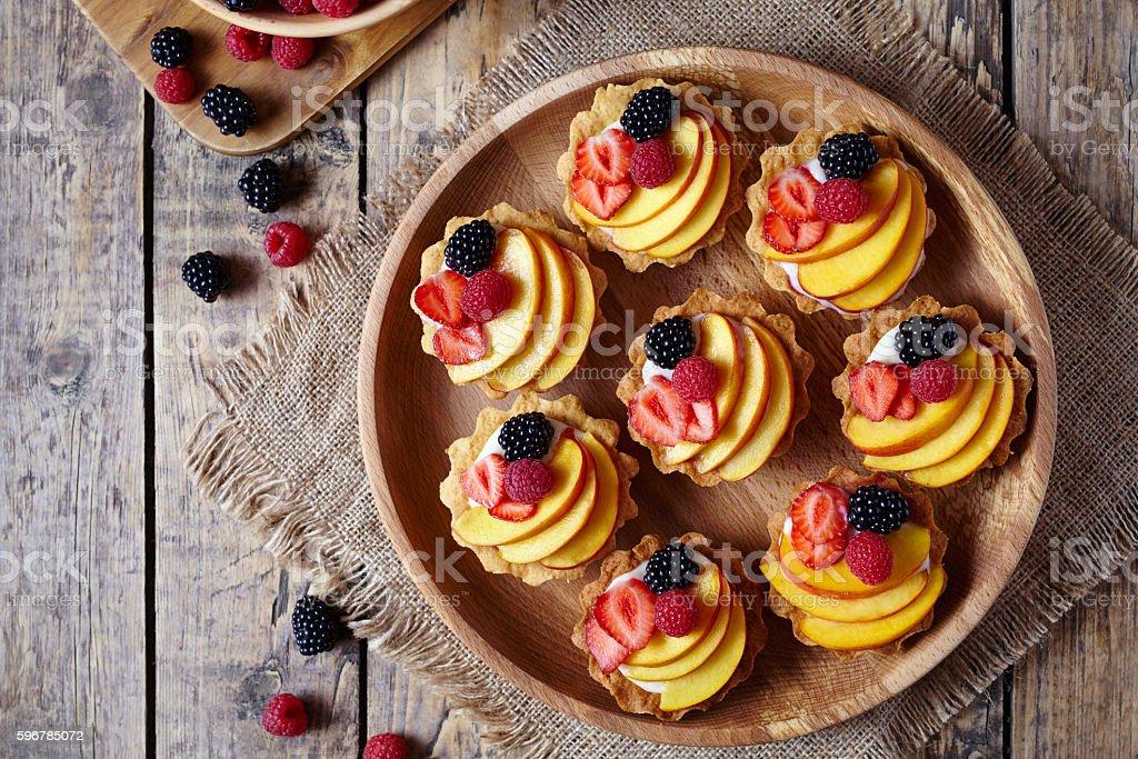 Fruit dessert tartlets with vanilla custard and fresh raspberries, blackberry stock photo