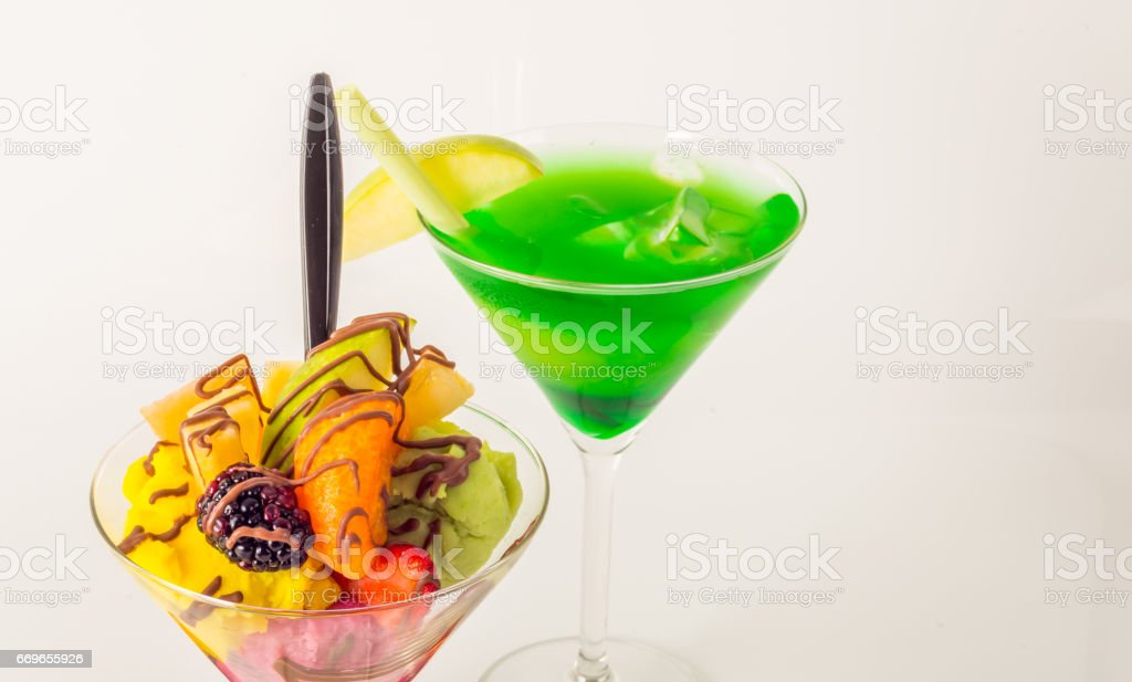 Fruit ice cream, decorated with fresh fruit, chocolate covered, green drink, martini glass stock photo