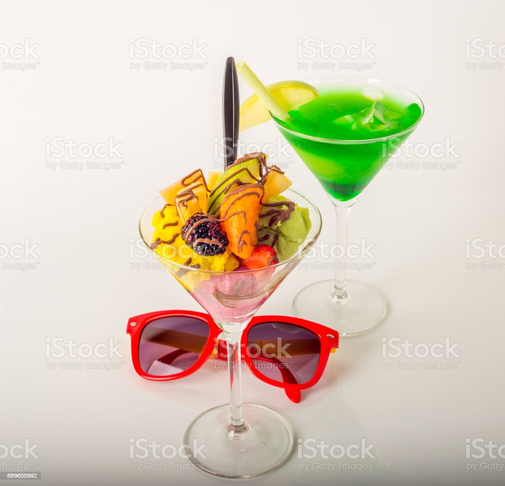 Fruit ice cream, decorated with fresh fruit, chocolate covered, green drink, martini glass, sunglasses stock photo
