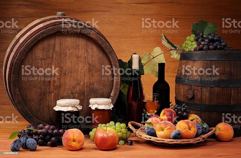 Fruit, jam, wine and wooden barrel stock photo