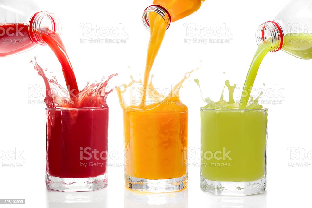 Fruit juices poured from bottles Kiwi, currants, orange stock photo