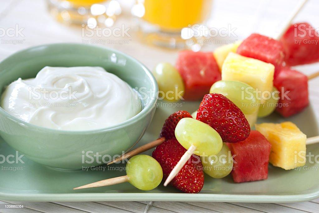 Fruit kebabs next to a bowl of yogurt royalty-free stock photo