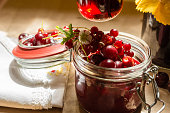 Fruit preserves and raw strawberries , cherries on   a kitchen table